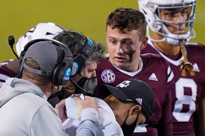 Mississippi State head football coach Mike Leach, left, confers with quarterback Will Rogers (2), right, while assistants listen during a game against Vanderbilt on Nov. 7 in Starkville, Miss.