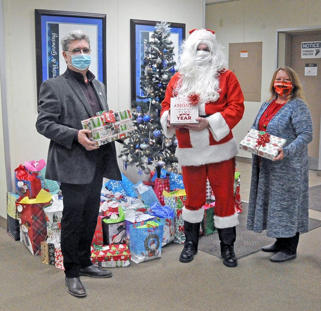 Tricor Industrial Inc. President Michael Stitzlein,  Josh Becker as Santa Claus and Tina Robertson stand by the tree with presents placed there by employees of the business. All the presents will be donated to residents of Hilltop Villa, an assisted living facility for those dealing with mental illness.