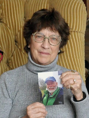 """Rita Dush holds a photo of her late husband Roger wearing """"his favorite outfit,"""" a winter vest and a baseball cap. Roger Dush died earlier this month due to a COVID-19 illness."""