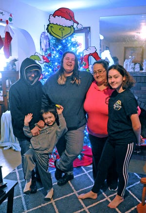 Chris Duffy, (from left) 5-year-old Randy Duffy, Rebecca Scott, Chrissy McKinney and Cirston Caine stand in front of the Christmas tree in McKinney's Wooster home. The Duffys and Scott are staying with McKinney and her children after their home caught fire in November.