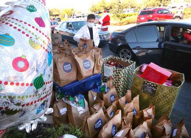 Dr. Ratan K. Ahuja grabs a bag of food for a family while a long line of cars snakes through the parking lot of the Florida Cardiopulmonary Center in Orange City on Friday, Dec. 18, 2020. Ahuja and his wife, Dr. Karuna Ahuja, funded Friday's event where about 500 bags of food and toys were given out to those in need.