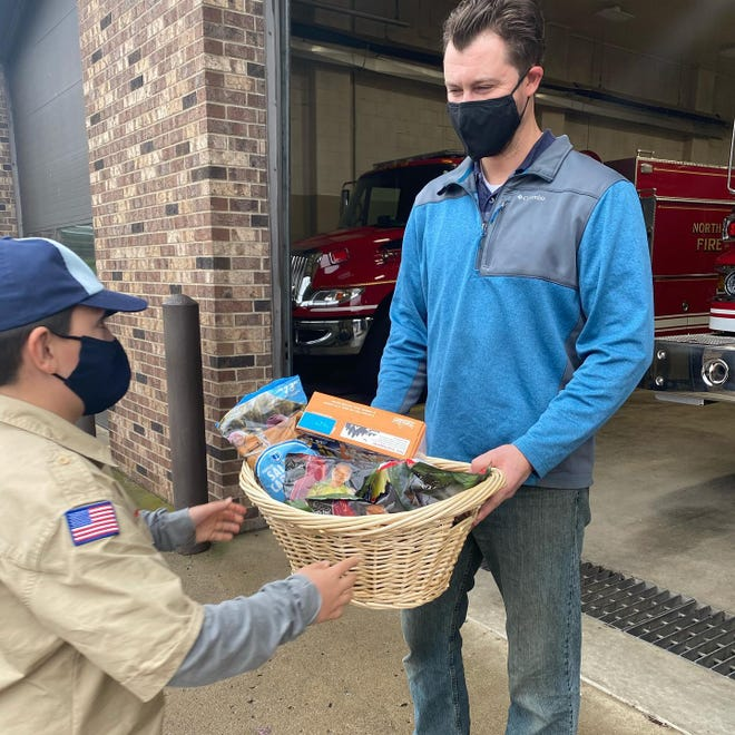 Cub Scouts Pack 402 in North Sewickley Township recently raised money to purchase gift baskets of popcorn to donate to local first responders. Pictured is Scout Bud Blyth, 10, delivering a basket to Bryan Paff, a firefighter with North Sewickley's volunteer fire department.