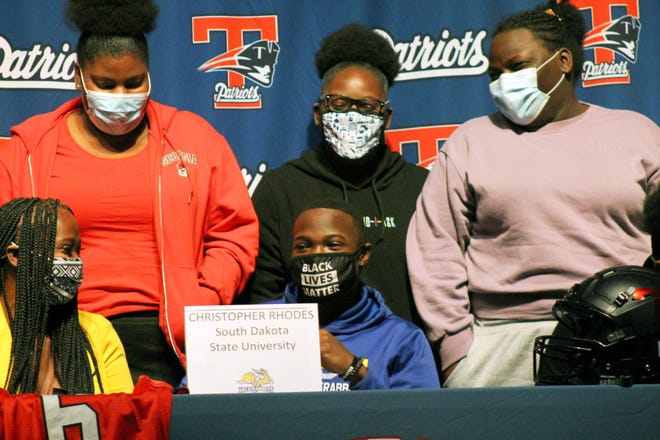 Truman defensive back Chris Rhodes celebrates with his family after signing to play football for South Dakota State University Thursday during a ceremony at the high school.