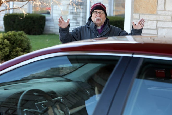 Pastor Paul Hermonsen blesses worshippers April 5 after they picked up palm leaves, during a drive through Palm Sunday service at Bethany Lutheran Church in Burlington. Like many local churches, Bethany Lutheran will host a parking lot service this Christmas Eve.
