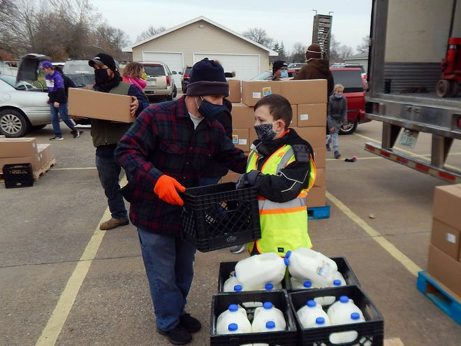 Lincoln Minard, 10, helps Pastor Simeon Counterman distribute milk Nov. 21 at Calvary Baptist Church, 2710 West Ave., in Burlington the Saturday before Thanksgiving. Minard and his father, Andrew, were among the dozens of volunteers handing out food boxes to people who flocked to the church in their cars. Counterman said the food, donated by the USDA's Farmers to Families Food Box Program, was an array of fresh fruit, dairy as well as a gallon of fresh milk. The church will give away another 1,200 boxes beginning 8 a.m. Saturday.
