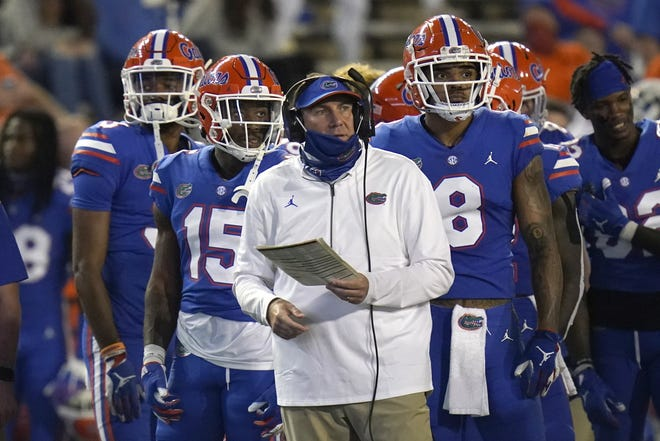 The Florida Gators and head coach Dan Mullen, seen here during a timeout in last week's 37-34 loss to LSU, were given a huge break by the College Football Playoff committee when UF dropped only one spot in the CFP rankings, preserving a chance to make the playoffs if it upsets Alabama in the SEC title game.