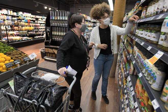Shopper Tracey Spruill gets help finding an item from cashier Trinity Thompson as Spruill shops for a senior friend at Native Sun Natural Foods Market on Thursday afternoon. Shoppers worked their way through the aisles of the Jacksonville Beach store wearing masks and maintaining social distancing rules.