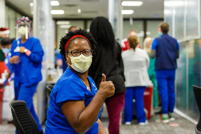 Tujuana Dudley, nurse manager on a COVID-19 unit at Baptist Medical Center South, gives the thumbs-up sign after being the first in line as Baptist Health began offering the COVID-19 vaccine to health care staff on Friday.
