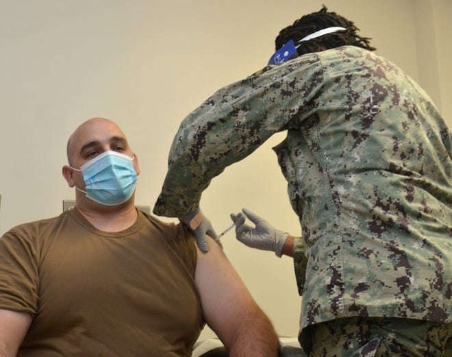 Hospital Corpsman 2nd Class Zachary Jawad, from Naval Hospital Jacksonville's preventive medicine team, receives the COVID-19 vaccine Thursday.