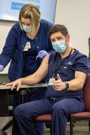 Dr. John Holder gives the thumbs-up as he receives one of the first COVID-19 vaccinations in Onslow County. Onslow Memorial Hospital began administering the vaccine Dec. 18 for frontline health care workers most at risk of exposure to the virus.