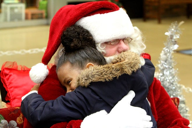 William Bumford of Freeport hugs a young girl in 2019 when he welcomed children at Lincoln Mall in Freeport. This year, Bumford is unable to listen to the wishes of children in a traditional way, but he does plan to make his presence known in the community in time for Christmas by donning his mask, suit and driving around the city.