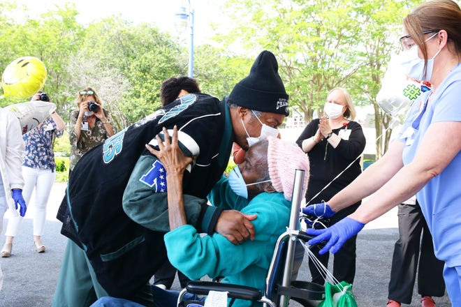 Gregory Darden kisses his mother, Mary Darden, on the forehead on April 28 after they were both released from UNC Lenoir Health Care after recovering from COVID-19.