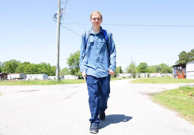 Cameron Knepper, a 16-year-old sophomore at North Lenoir High School, walks in his neighborhood in La Grange Tuesday, April 14, but he no longer has to walk or bike to school for Wi-Fi.