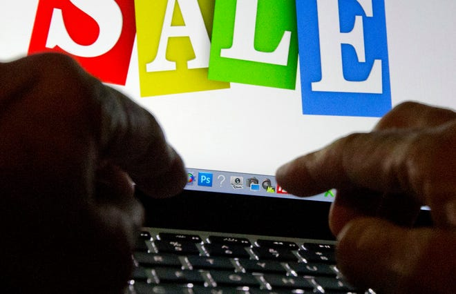 In this Dec. 12, 2016 file photo, a person in Miami searches the internet for sales. Online shopping scams are on the rise as thieves look to take advantage of the increase in people shopping online during the pandemic.