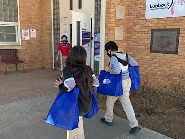 Students carried in donated bags of food from University Medical Center and UMC EMS employees Thursday at Brown Elementary in Lubbock.