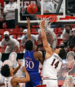 Kansas' Ochai Agbaji (30) shoots the game-winning shot around Texas Tech's Marcus Santos-Silva (14) during the second half of a Big 12 Conference game Dec. 17 against the then-No. 5 Jayhawks at United Supermarkets Arena. The then-No. 14 Red Raiders lost 58-57.