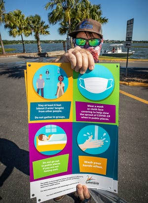 City Of Lakeland Parks and Recreation employee Nathan Geiger holds up some Covid-19 guidelines he was posting at the Lake Hollingsworth Boat Ramp as parks and trails reopened in Lakeland in May.