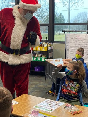 CEL art teacher Greg Hoffert plays Santa Friday and gives a fist bump to second grade student Savannah Patinga. Hoffert wished all lower grade classes a Merry Christmas prior to the start of Christmas break.