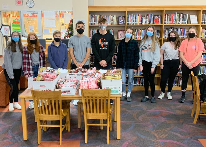 Leo Club members take a moment off from assembling and wrapping gift bags for a group photo.