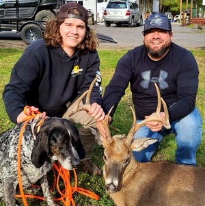 Jesse Hockaday (left), and John Hockaday (right), pose with their dog Annie Mae with a buck they recovered on Dan's Mountain in Allegany County.