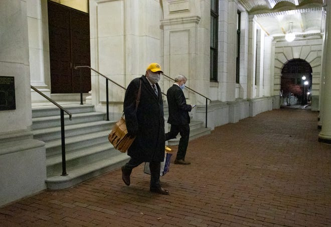 House Speaker Robert DeLeo exited the State House Wednesday night clad in a Bruins cap and accompanied by House legal counsel James Kennedy, right. DeLeo silently got into his car without answering questions about whether he would be stepping down.