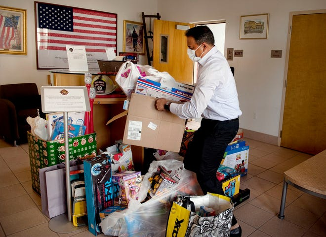 Deputy Town Manager Jay Boodheshwar carries toys collected during the Town of Palm Beach United Way toy drive to be delivered to Families First and Literacy Coalition at the Central Fire Station on Tuesday.