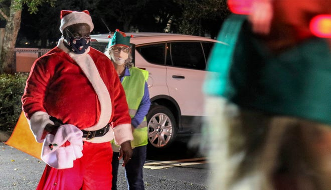 Tony Nelson, dressed as Wellington's first Black Santa welcomes vehicles at the village's drive-thru food and gift card distribution Thursday night in Wellington. Wellington provided a week's worth of food from Feeding South Florida and a $25 gift card for each of the 600 vehicles that registered for the event. KRISTINA WEBB/PALM BEACH POST
