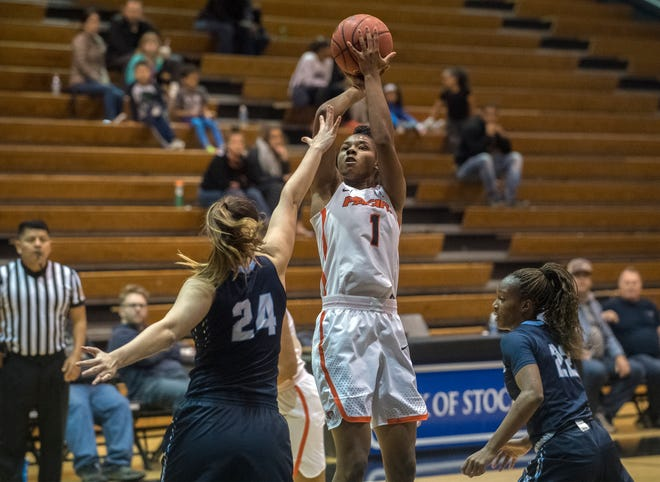 Pacific's Brooklyn McDavid, right, shoots over San Diego's Caroline Buhr during a women's basketball game at Pacific's Spanos Center in Stockton.