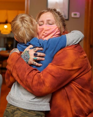 Otto Cunningham, 7, gives his mother, Kate, a hug in his family's home in Ravenna.