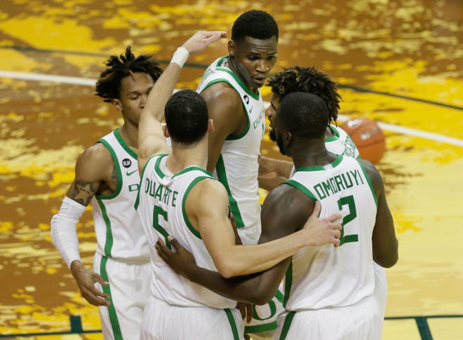 Oregon players come together at the top of the key during the first half of their game against San Francisco.