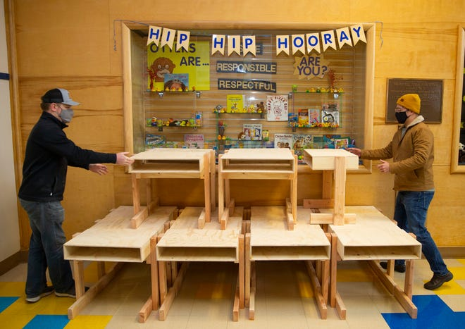 Andrew Moreland, left, and Conrad Hulen deliver some of the 60 desks they have built for children to use while studying remotely during the pandemic closures to the lobby of Two Rivers-Dos Ríos Elementary in Springfield.