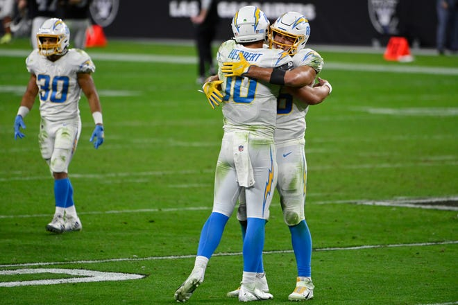Los Angeles Chargers quarterback Justin Herbert is embraced by tight end Hunter Henry, right, after Herbert ran for the game-winning touchdown in the Chargers' 30-27 win over the Las Vegas Raiders on Thursday.
