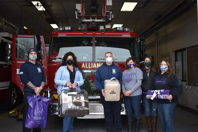 Alliance firefighters and staff from the University of Mount Union on Friday show off some of the blankets they collected as part of Project Warm Blanket. Among the people involved in the drive were, from left, Brian Anderson, Stephanie Salamon, Chris Johnson, Chris Pontius, Stephanie Helmick and Jody Bryan.