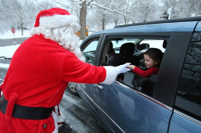 Santa holds the hand of Aislyn Burcham during a drive-through Christmas Party hosted by Regina Coeli preschool teachers and staff Friday, Dec. 18, 2020, in Alliance. It was held at the home of Kelli Berry, pre-school director and teacher at the school.