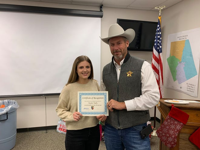 The Erath County Sheriff's Office recently held its office holiday party and presented year-end awards. Taylor Tully received Dispatcher of the Year and is presented a certificate by Sheriff Matt Coates.