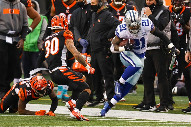 Dallas Cowboys running back Ezekiel Elliott (21) tries to stay in bounds as he's pursued by Cincinnati Bengals free safety Jessie Bates (30) in the second half in Cincinnati on Sunday.