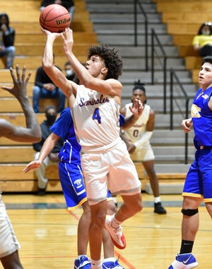 Southeast's Malik Banks (#4) scores two points over the Bayshore Bruins during a district home game on Thursday, Dec. 17, 2020.