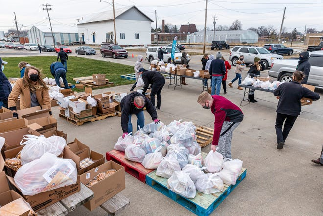Volunteers load bags of food into position to distribute to anyone in need during a food distribution by the Central Illinois Foodbank with food provided by Dot Foods Inc. as cars line up down West Lafayette Avenue for pickup Friday, Dec. 18, 2020, in Jacksonville. The food distribution served over 270 cars, which included multiple families per car at times.