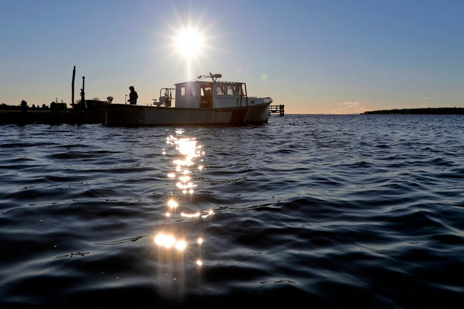 The sun rises in the distance as a fisherman prepares to pull his lobster boat out of the water in Mattapoisett.