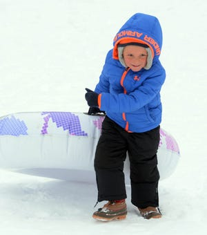 Brigham Nowak, 5, of Montville, brings his tube back up the hill for another run Friday at the Norwich Golf Course.