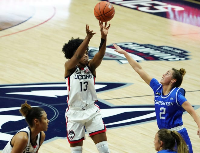 Connecticut guard Christyn Williams (13) shoots against Creighton guard Tatum Rembao (2) in the first half of an NCAA college basketball game in Storrs on Thursday. [David Butler II/Pool photo via AP]