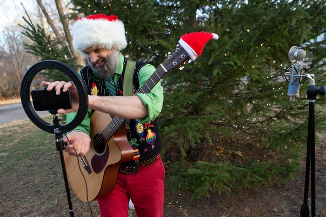"""Dressed in holiday attire, Kyle Moreland sets up his phone to record a music video outside his home Thursday afternoon. For 15 years, Moreland has put on a local concert and this year adapted by creating """"A Very Merry Kyle Moreland Christmas"""" series of videos and songs posted on Facebook leading up to Christmas."""