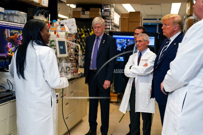 FILE - In this Tuesday, March 3, 2020 file photo, Dr. Kizzmekia Corbett, left, senior research fellow and scientific lead for coronavirus vaccines and immunopathogenesis team in the Viral Pathogenesis Laboratory, talks with President Donald Trump as he tours the Viral Pathogenesis Laboratory at the National Institutes of Health in Bethesda, Md. Corbett, who is from Orange County, is credited with helping develop the Moderna vaccine for COVID-19. (AP Photo/Evan Vucci)