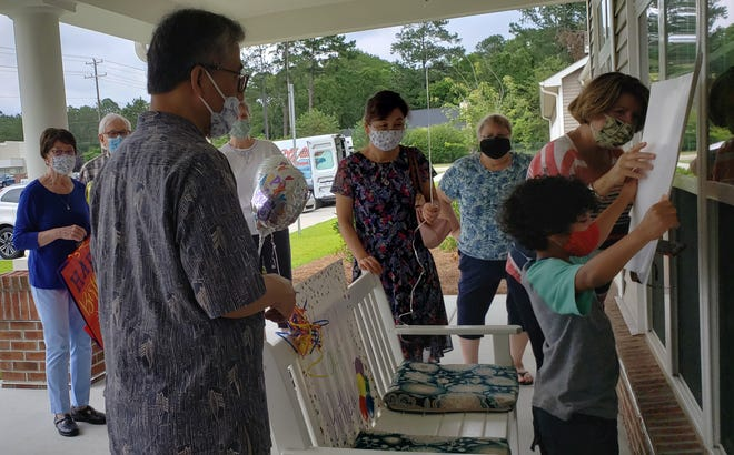 Members of Camp Ground United Methodist Church visit a church member at an assisted-living facility in June, 2020.