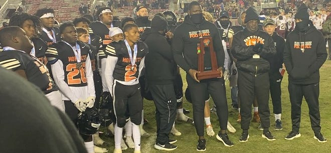 Hawthorne football coach Cornelius Ingram holds the Class 1A runner-up trophy Thursday following the Hornets' 27-14 loss to Baker at Doak Campbell Stadium in Tallahassee.