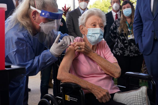 Nurse Christine Philips, left, administers the Pfizer vaccine Wednesday to Vera Leip, 88, a resident of John Knox Village in Pompano Beach. Nursing home residents and health care workers in Florida began receiving the Pfizer vaccine this week.
