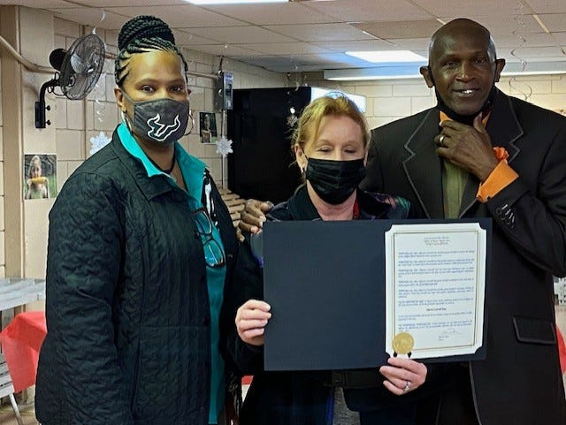 From left, District 1 Gainesville City Commissioner Gigi Simmons, Marcia Conwell, president and CEO of Bread of the Mighty Food Bank and Prophet George Young, a volunteer at the food bank at a program to honor Conwell for her work to end hunger . Simmons presented Conwell with a proclamation from the city of Gainesville last Thursday. [Photo by Aida Mallard/For The Guardian]