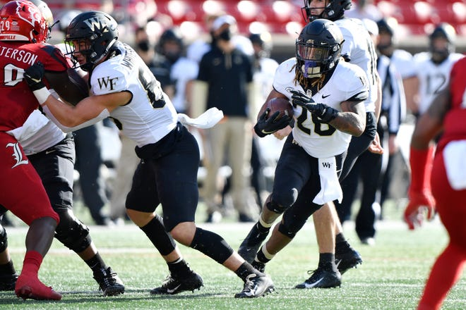 Wake Forest running back Christian Beal-Smith, right, hits the running lane in a game against Louisville last Saturday.