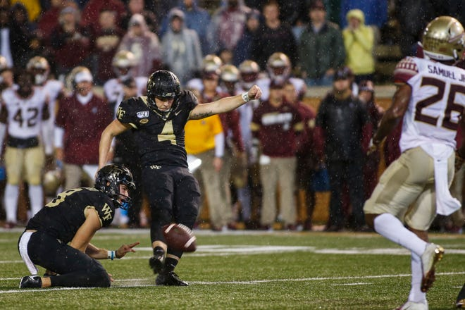 Wake Forest kicker Nick Sciba, middle, kicks the go-ahead and eventual game-winning field goal as Dom Maggio, left, holds against Florida State last season.