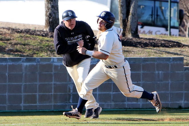 UAFS baseball coach Todd Holland, left, runs with Brooks Sunny down the third base line as Sunny heads for home, Friday, Feb. 28, 2020, during a game at Crowder Field.